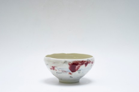Porcelain bowl with resist decoration and oxblood glaze. 14cmw x 10cmh